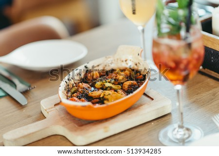 covered Turkish restaurant table with a shrimp and veggies casserole and  cocktail