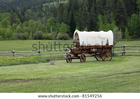 covered wagon in green field near trees and fence - stock photo
