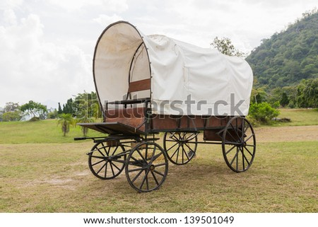 Covered wagon with white top in park - stock photo