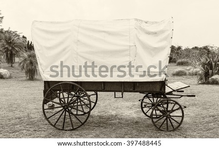 Covered wagon with white top in park vintage style - stock photo