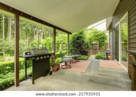 Covered walkout deck with patio area and landscape - stock photo