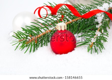 covered with snow branch of a Christmas tree and red ball on snow background - stock photo