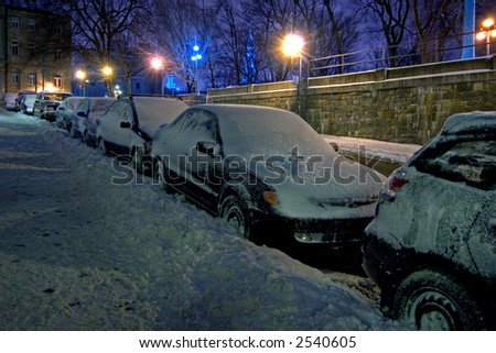 Covered with snow cars parked at roadside - stock photo