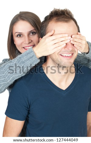 Covering her man's eyes to surprise him - stock photo