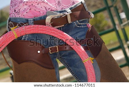 Cow girl Fashion, horseback riding apparel, rope, lasso, brown leather chaps, denim blue jeans, western belt buckle, pink blouse shirt - stock photo