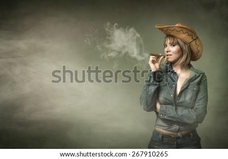 cow girl smokes big cigar in a cloud of fog - stock photo
