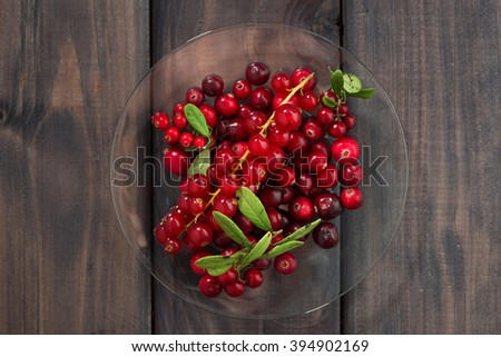 cowberries and red currants in a glass plate, top view, horizontal - stock photo