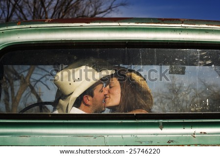 Cowboy and girlfriend kissing in through the back window of a pickup truck - stock photo
