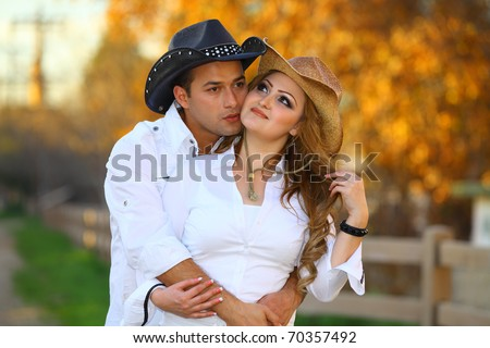 Cowboy and his cowgirl romantically kissing, - stock photo