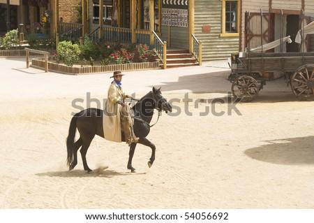 Cowboy bandit riding into town - stock photo