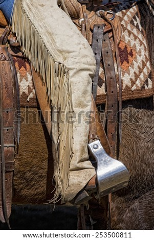 Cowboy boot in stirrup riding at roundup - stock photo