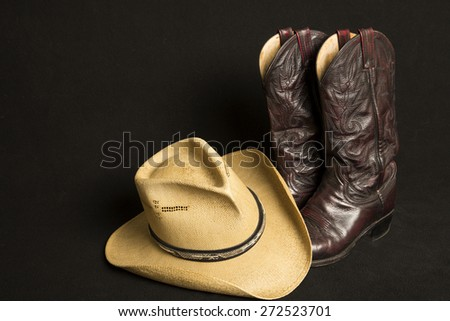 Cowboy boots and cowboy hat on black background - stock photo