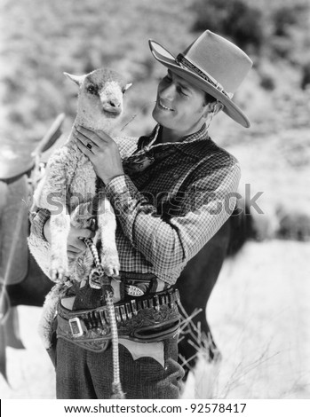 Cowboy carrying a lamb and smiling - stock photo