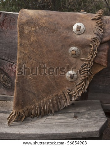 Cowboy chaps detail with old weathered leather and fringe. Grunge intact. - stock photo