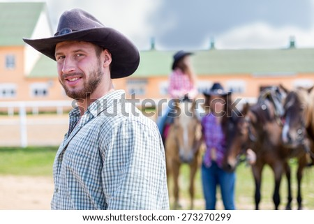 cowboy closeup portrait on background of horses - stock photo