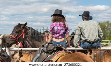 cowboy couple sit back  and behold horses - stock photo