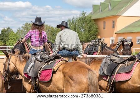 cowboy couple sit back stroking horses - stock photo