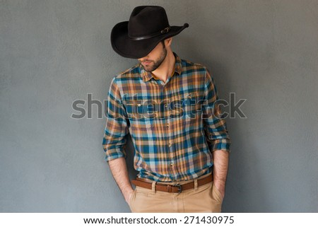 Cowboy couture. Portrait of young man wearing cowboy hat and looking down while standing against grey background  - stock photo