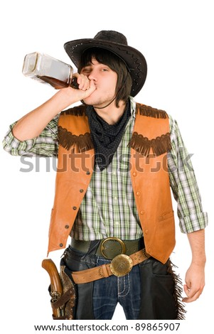 Cowboy drinking whiskey from the bottle. Isolated - stock photo