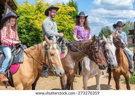cowboy family of four on horses - stock photo