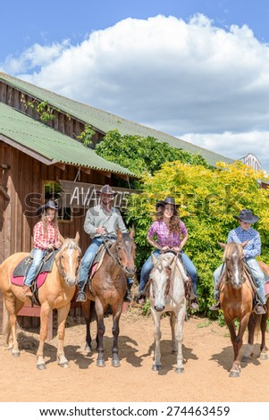 cowboy family of four on horses on background of wooden building - stock photo