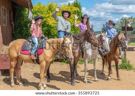 cowboy family of four on horses waving their hands
