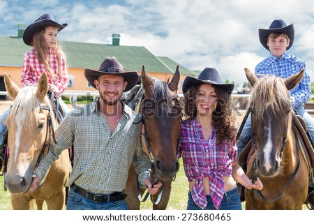 cowboy family of four with horses closeup - stock photo
