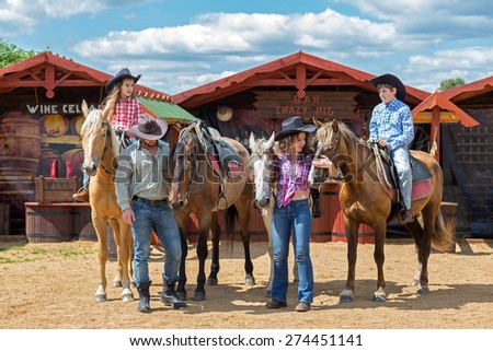 cowboy family of four with horses on background of paddock - stock photo
