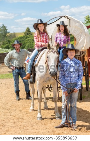 cowboy family of four with wagon and horse - stock photo