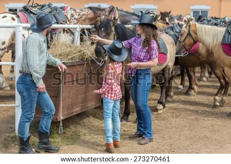 cowboy family of three feed the horses hay - stock photo