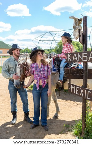 cowboy family of three looking at a scull on signpost - stock photo