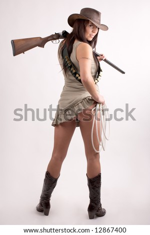 Cowboy girl. Art shot of a pretty model with shot gun. - stock photo