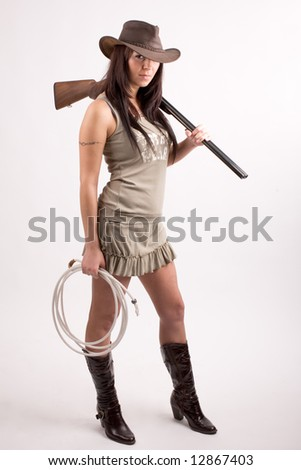 Cowboy girl. Art shot of a pretty model with shot gun