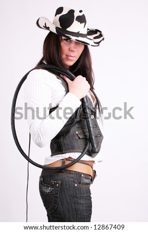 Cowboy girl. Art shot of a pretty model with whip. - stock photo