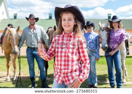 cowboy girl with ok gesture closeup portrait on background of her family with horses - stock photo