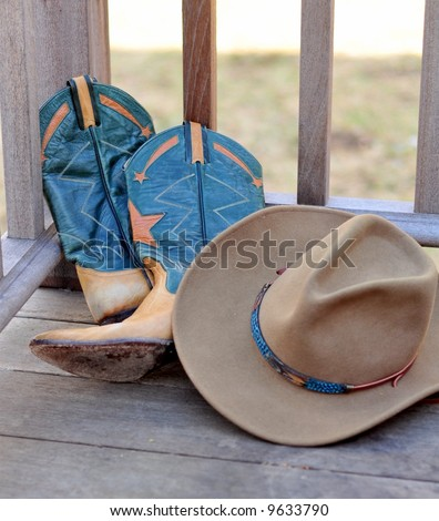 Cowboy Hat and boots leaning against railing - stock photo