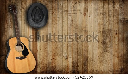 Cowboy hat and guitar against an old barn background. - stock photo