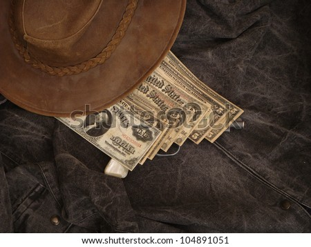 Cowboy Hat and Large Old Paper Money over Gun - stock photo