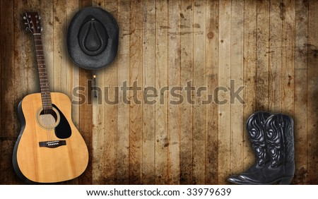 Cowboy hat, boots and guitar against an old barn background. - stock photo