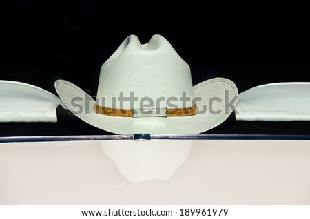 Cowboy hat displayed on the back of a car window against dark background, vintage filter effect - stock photo