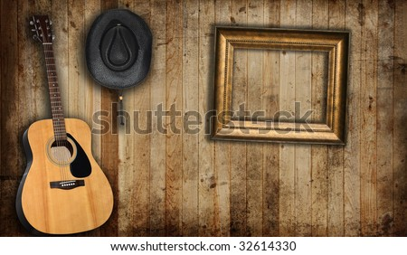 Cowboy hat, guitar and empty picture frame, against an old barn background. - stock photo