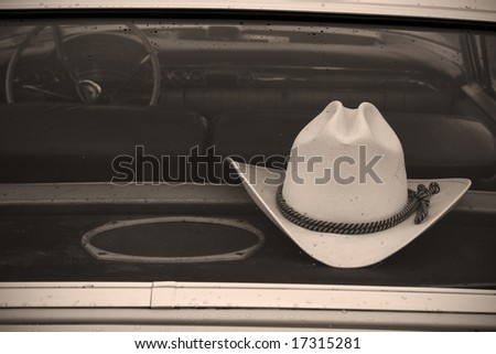 cowboy hat in car, with raindrops on rear window - stock photo