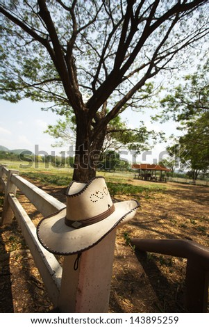 cowboy hat, light brown cowboy hat hanging on farm fence - stock photo