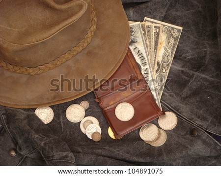 Cowboy Hat over  Wallet Overflowing with Large Paper Money, Silver and Gold Coins - stock photo