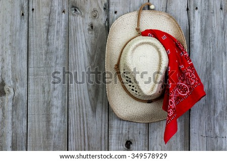 Cowboy hat with red bandanna hanging on antique rustic wooden background - stock photo