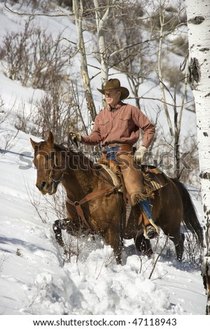 Cowboy in chaps riding a horse in the snow. Vertical shot. - stock photo