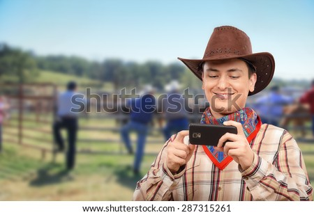 Cowboy in colored bandana has just made photos with smart phone. Now he looks them with pleasure. Young man is wearing brown cowboy hat and plaid shirt - stock photo