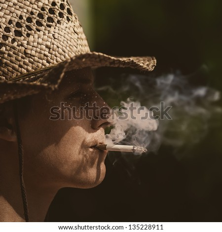cowboy in hat with cigar silhouette - stock photo