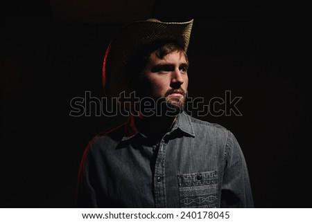 Cowboy in Studio Lighting looking at light to the left dark - stock photo
