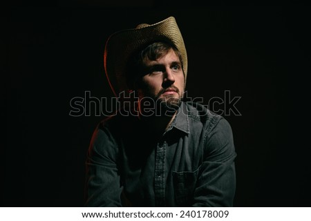 Cowboy in Studio Lighting serious face leaning over chair looking at light